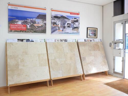 Trois planches d'échantillons avec différents types de travertin appuyées contre un mur blanc