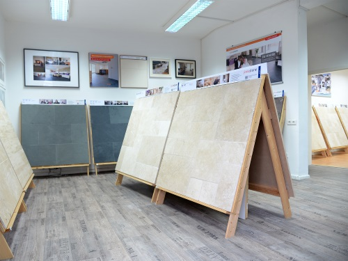 Salle d'exposition avec plusieurs échantillons de panneaux en travertin et ardoise